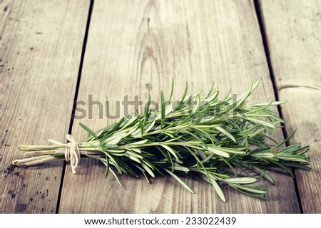 Fresh bunch of rosemary on wooden table. Aromatic evergreen herb, many culinary and medicinal uses. Copyspace. - stock photo
