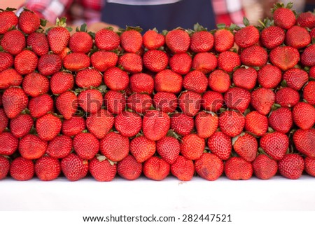 Fresh bunch of vivid strawberries in a market - stock photo