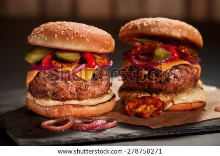 Fresh burger closeup on black slate - stock photo