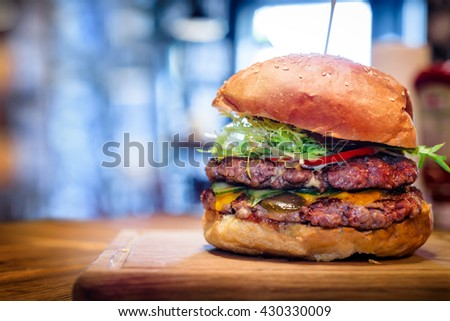 Fresh burger closeup on wooden table. Selective focus on the centre of the burger. - stock photo