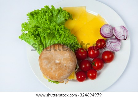 Fresh burger in plate with vegetables and french fries.Big hamburger. Ingredients for hamburgers. Top view - stock photo