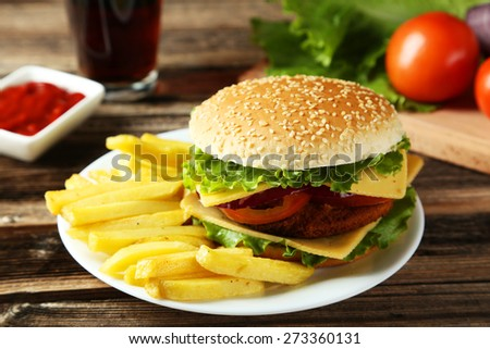 Fresh burger on plate on brown wooden background