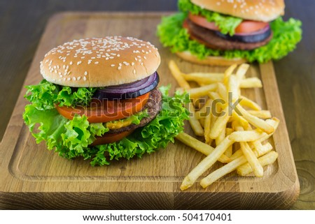 Fresh Burger with Beef Cutlet Onion Lettuce Tomato Mustard Sauce and French Fries on Wooden Table. Horizontal, Selective Focus