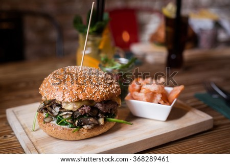 Fresh burger with carrot fries and salad on wooden table. - stock photo