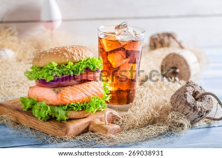 Fresh burger with fish  served with cold drink - stock photo