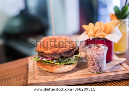 Fresh burger with french fries and salad on wooden table. - stock photo