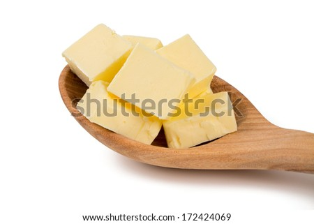fresh butter in a wooden spoon isolated on white