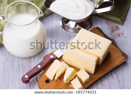 Fresh butter on wooden board, milk, sour cream  on white table. Selective focus. Rustic style. - stock photo