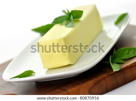 Fresh Butter stick on a white dish with basil leaves,close up - stock photo