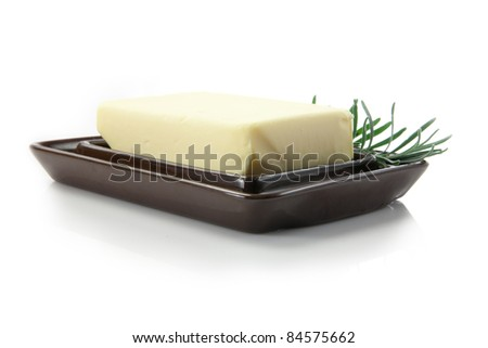 fresh butter with rosemary decoration in butter dish - stock photo