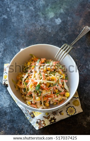 Fresh cabbage, corn and carrot coleslaw salad in bowl, mayonnaise dressing. Dark background, top view, closeup, copy space