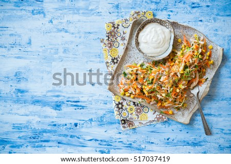 Fresh cabbage, corn and carrot coleslaw salad on rustic plate, mayonnaise dressing on side. Blue background, top view, copy space