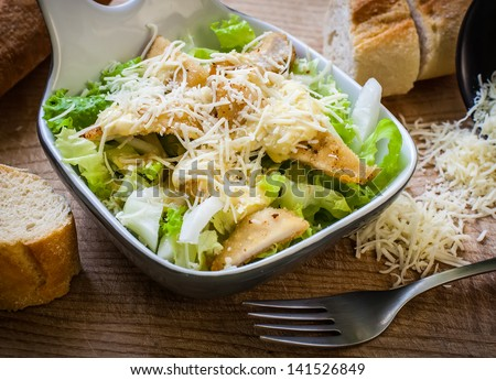 fresh caesar salad on bowl with parmesan cheese - stock photo