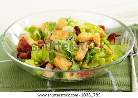 Fresh caesar salad with croutons and bacon bits served in a glass bowl