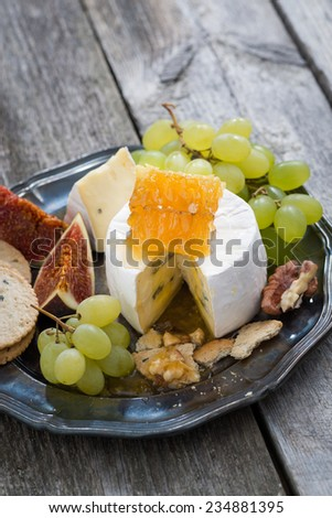 fresh camembert with honey, grapes and crackers on a plate, vertical, close-up