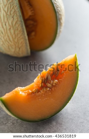 Fresh cantaloupe melon cutting on grey table. Appetizing, delicious, freshness, sweet summer dessert. Healthy, ripe, juicy fruit closeup. Copy space - stock photo