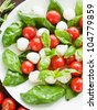 Fresh caprese salad with cherry tomatoes, baby basil and mozzarella. Shallow dof. - stock photo