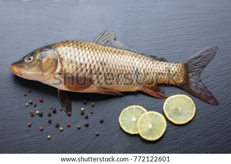 Fresh carp with peppers and lemon on black cutting board