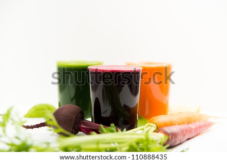 Fresh Carrot, Beets, and Greens Juices on White Background - stock photo