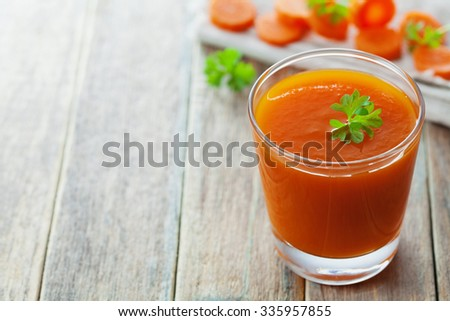 Fresh carrot juice in glass on wooden table, healthy vegetable drink