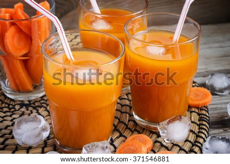 Fresh carrot juice with ice, selective focus - stock photo