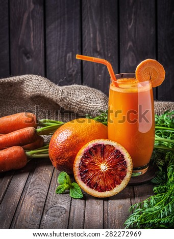 Fresh carrot juice with oranges at wooden background - stock photo