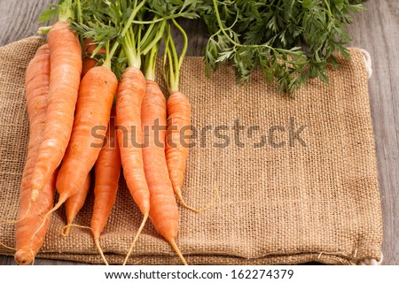 Fresh carrot with green leaves on jute bag - stock photo