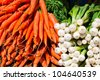 Fresh carrots and onions in the grocery market. - stock photo