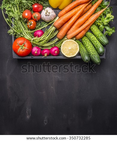 fresh carrots cherry tomatoes, garlic, cucumber, lemon, pepper, radish, wooden spoon salt pepper colored, oil wooden rustic background top view close up border, place for text  - stock photo