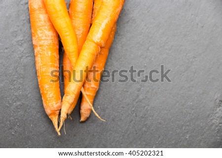 fresh carrots on dark slate - stock photo