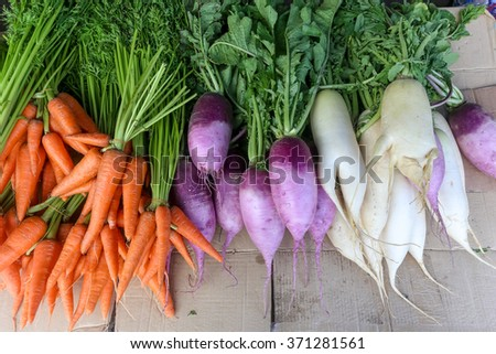 Fresh carrots on market table - stock photo