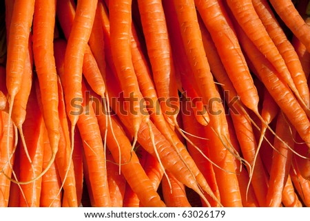 Fresh carrots piled high on a market stall - stock photo