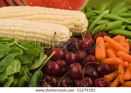 Fresh carrots,sugar snap peas, white corn,rhubarb, watermelon, baby spinach and cherries make up this healthy grouping of fruits and vegetables. - stock photo