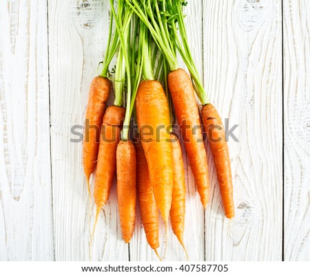 Fresh carrots with green leaves stalks or haulm on white  wood background - stock photo