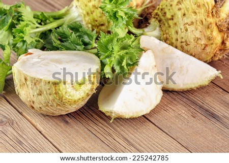Fresh celery root on a wooden board, one cut. - stock photo