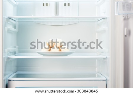 Fresh champignon mushrooms on white plate in open empty refrigerator. Weight loss diet concept. - stock photo