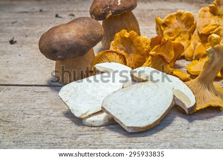 Fresh Chanterelle and Boletus Edilus mushrooms on a wooden table - whole and sliced - stock photo