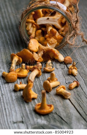 fresh chanterelle mushrooms from glass jar on old wooden table