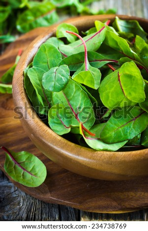 Fresh chard leaves in wooden bowl - stock photo