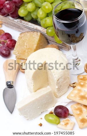 fresh cheese, crackers, grapes and a glass of wine, top view, vertical