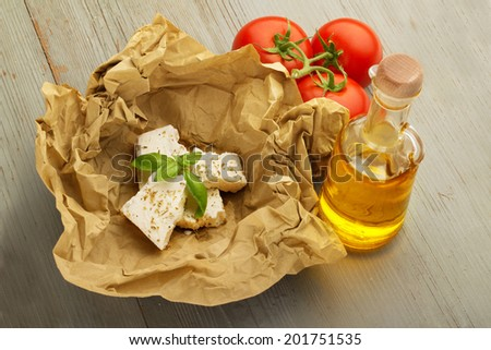 fresh cheese in a paper wrapper, tomatoes and olive oil - stock photo