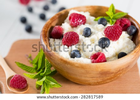 Fresh cheese in a wooden bowl with berries collected