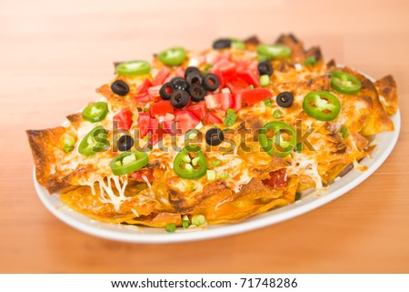 Fresh cheese nacho with vegetable on the top. Very shallow depth of field. - stock photo