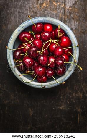Fresh cherries berries in blue bowl on dark rustic wooden background - stock photo