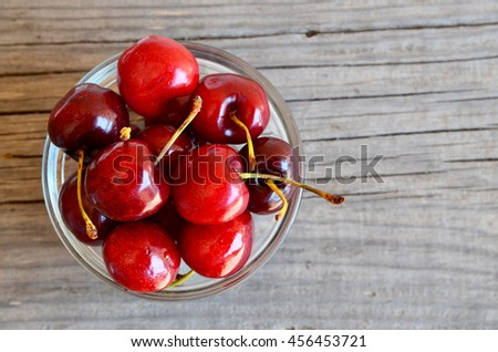 Fresh cherries berries in glass bowl on old wooden background.Selective focus.Top view.
