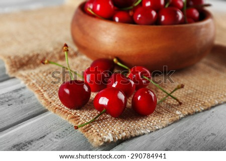 Fresh cherries in bowl with sackcloth on wooden table, closeup