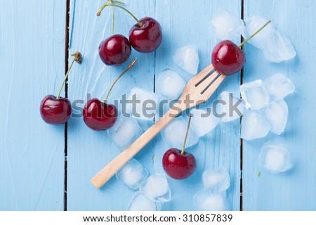 fresh cherries on wooden table - stock photo