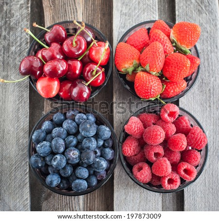 Fresh cherry, strawberry, blueberry and raspberry in a bowls on wooden table - stock photo