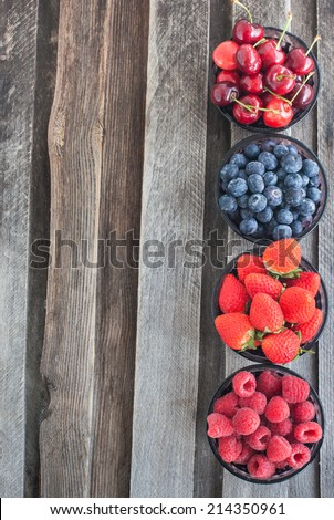 Fresh cherry, strawberry, blueberry and raspberry on wooden table, copy space - stock photo