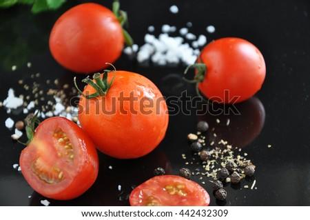 Fresh cherry tomato and spice on black background - stock photo